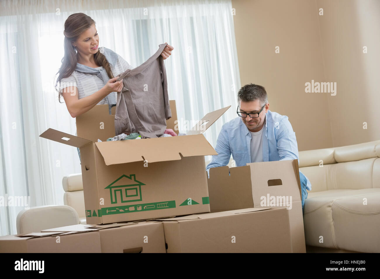 Mid-adult couple unpacking cardboard boxes in new home - Stock Image