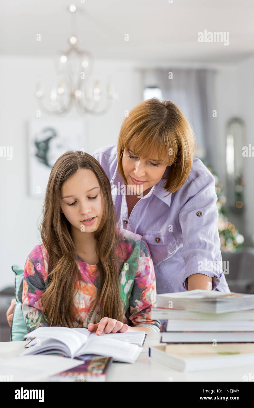 Mother guiding daughter in doing homework at table - Stock Image