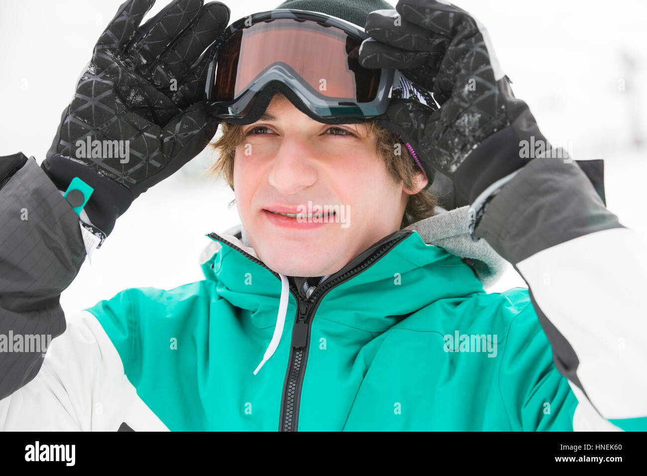 Handsome young man wearing ski goggles outdoors - Stock Image