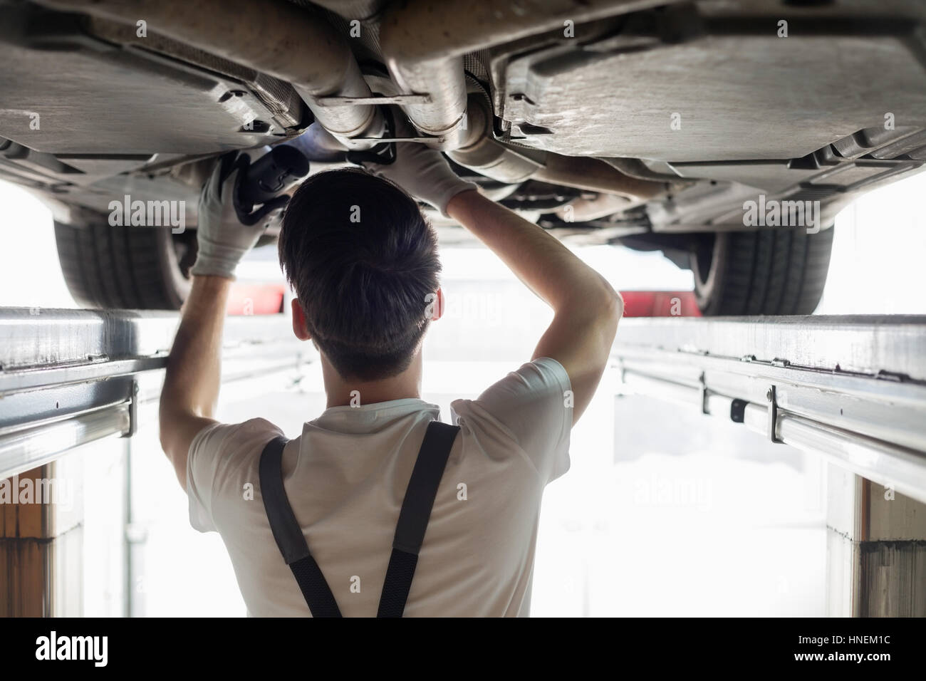 Rear view of automobile mechanic examining car in workshop - Stock Image