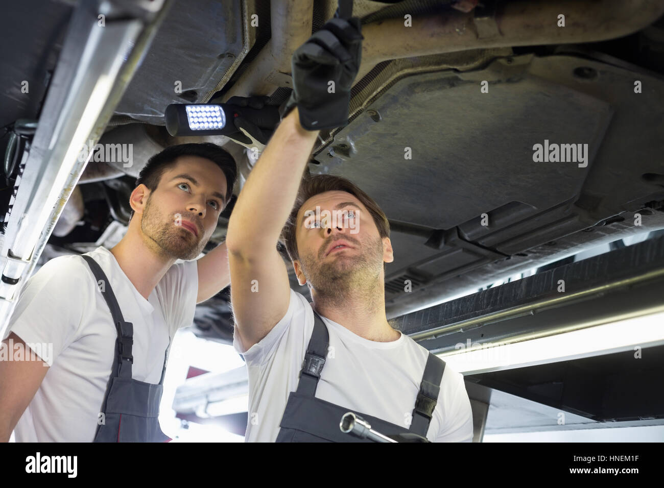 Male mechanics examining car in workshop - Stock Image