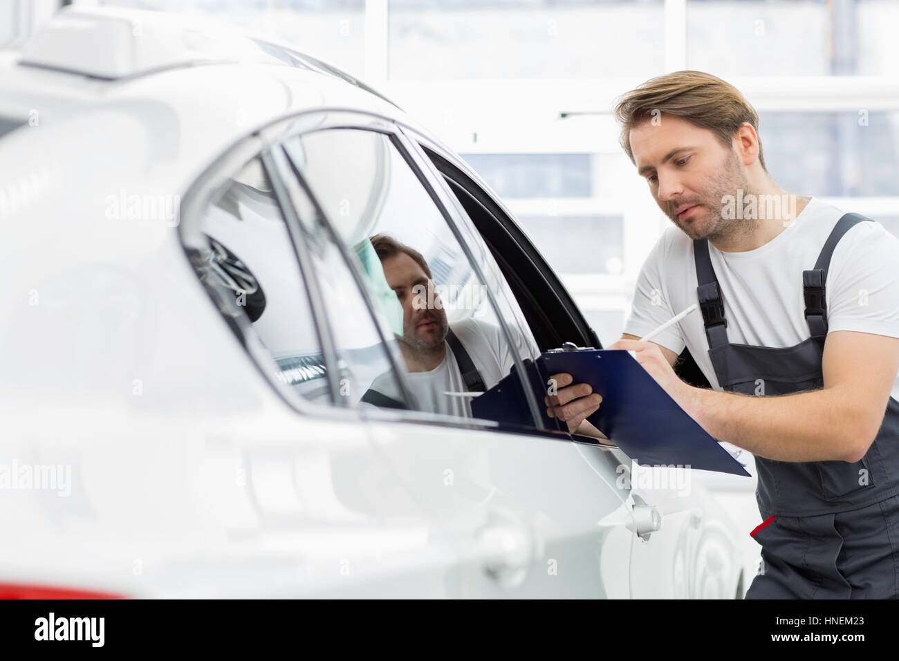 Automobile mechanic writing on clipboard while examining car in repair shop - Stock Image