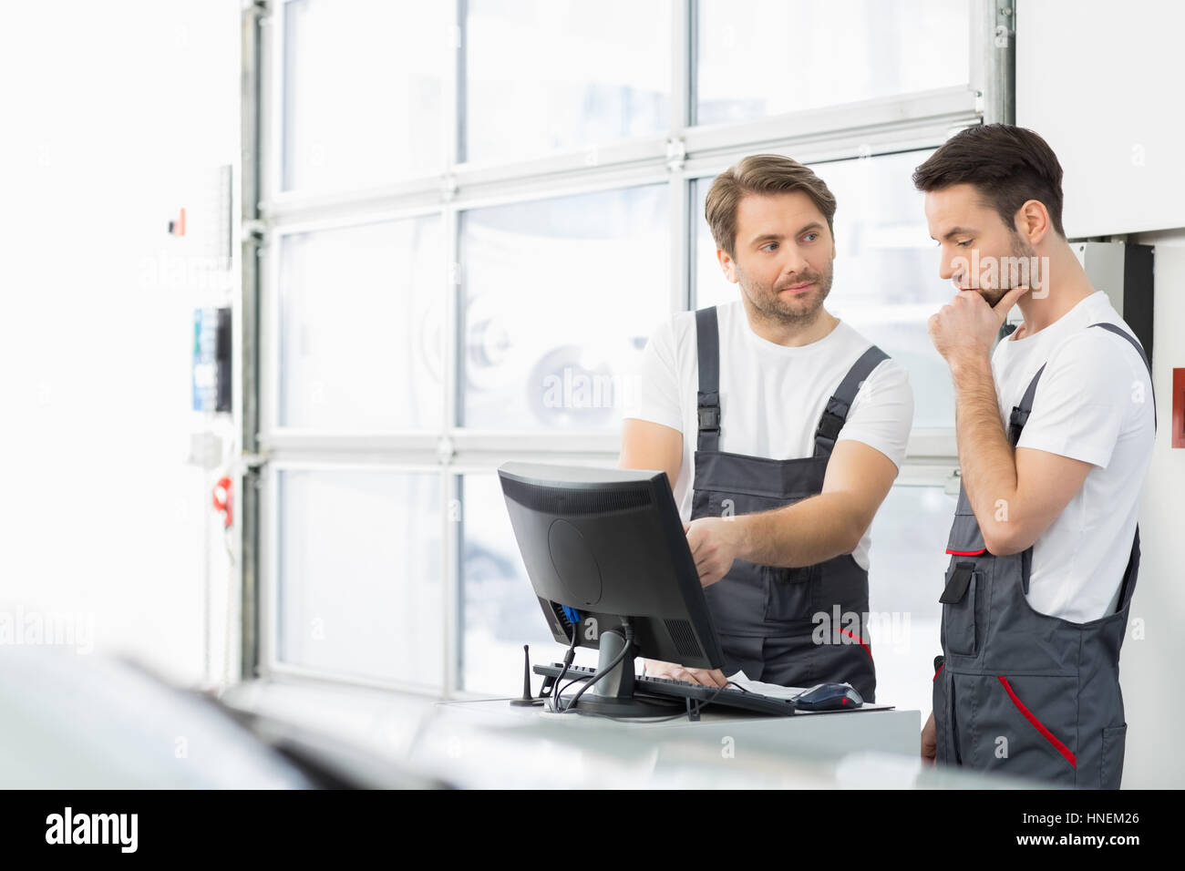 Male automobile mechanics conversing in repair shop - Stock Image
