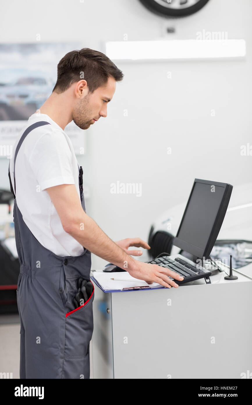 Side view of automobile mechanic using computer in workshop - Stock Image