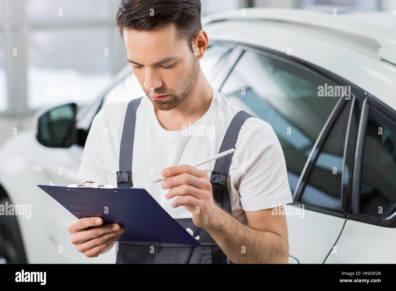 Young male maintenance engineer holding clipboard in repair shop - Stock Image