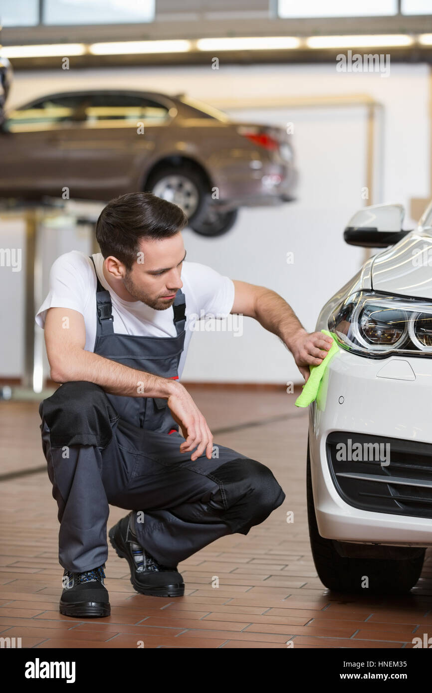 Full length of automobile mechanic cleaning car in workshop - Stock Image