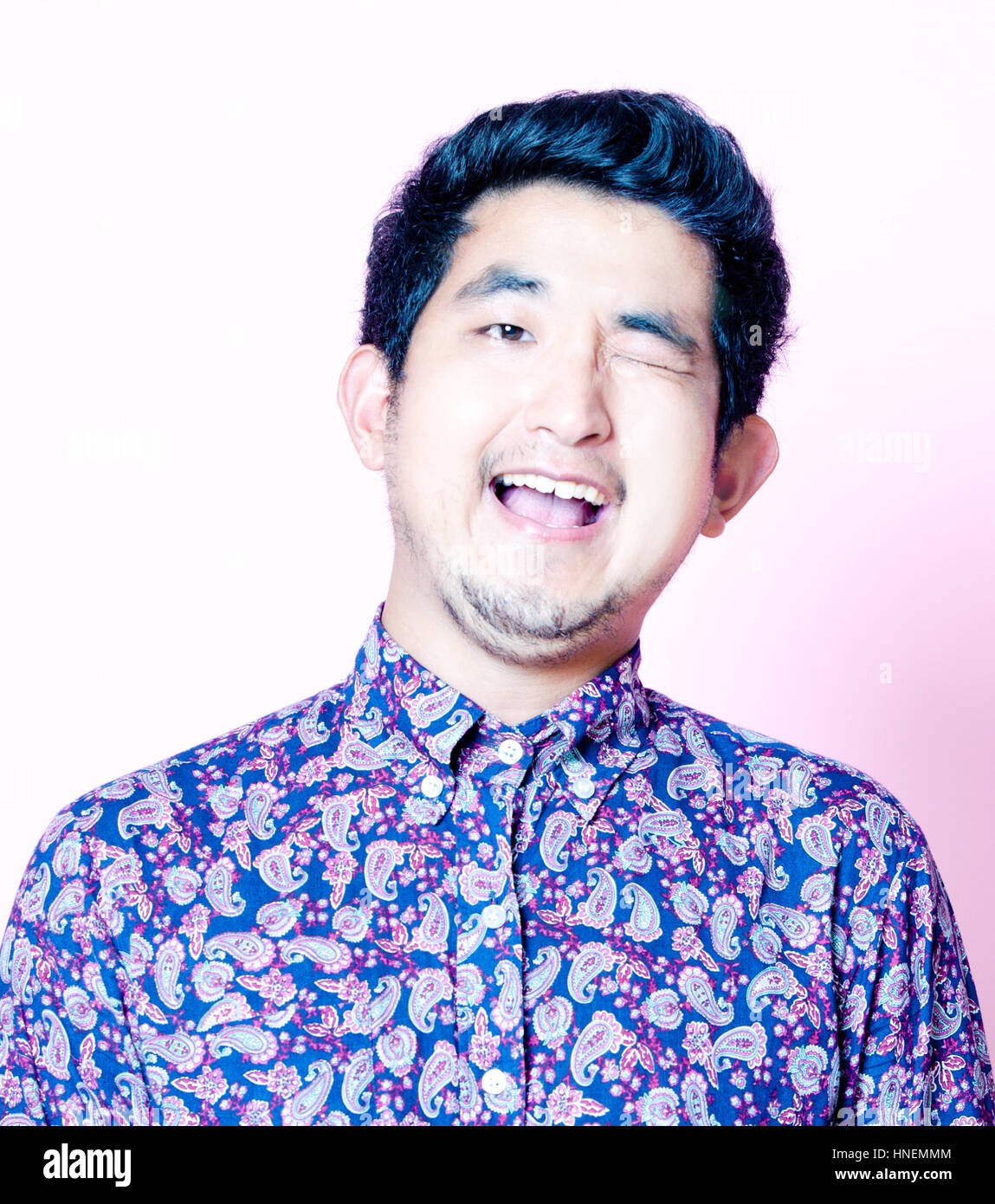 Young Geeky Asian Man in colorful shirt - Stock Image