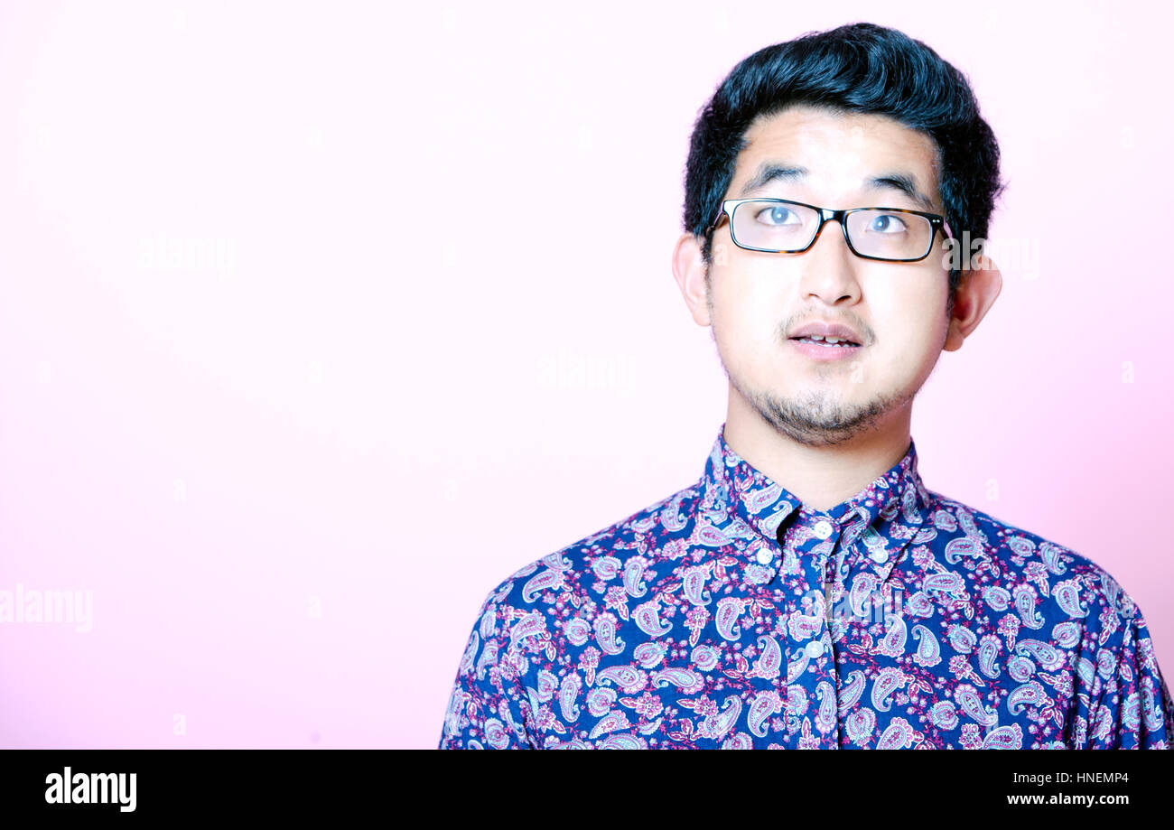 Young Geeky Asian Man in colorful shirt wearing glasses - Stock Image