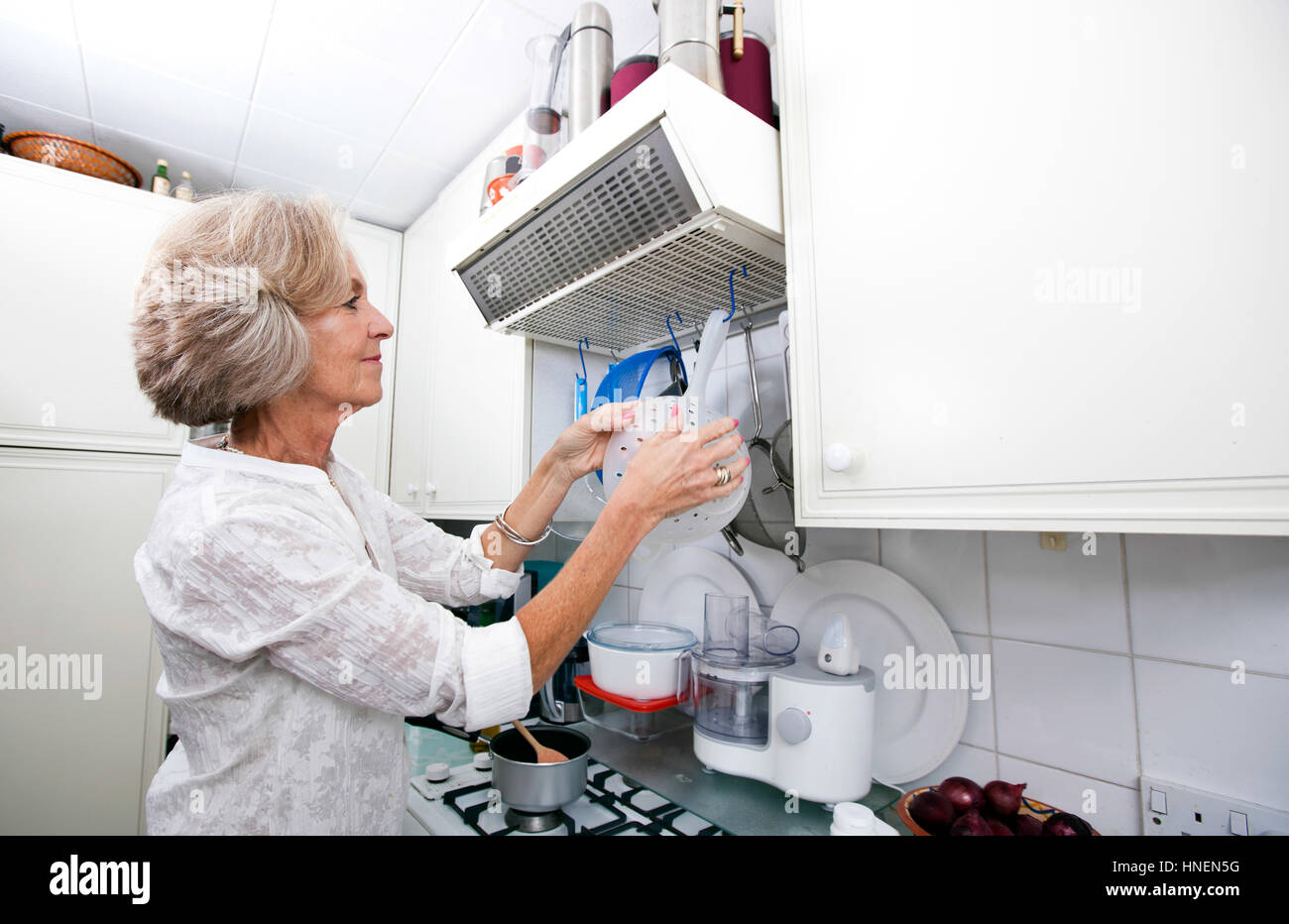 Senior woman hanging colander in domestic kitchen - Stock Photo