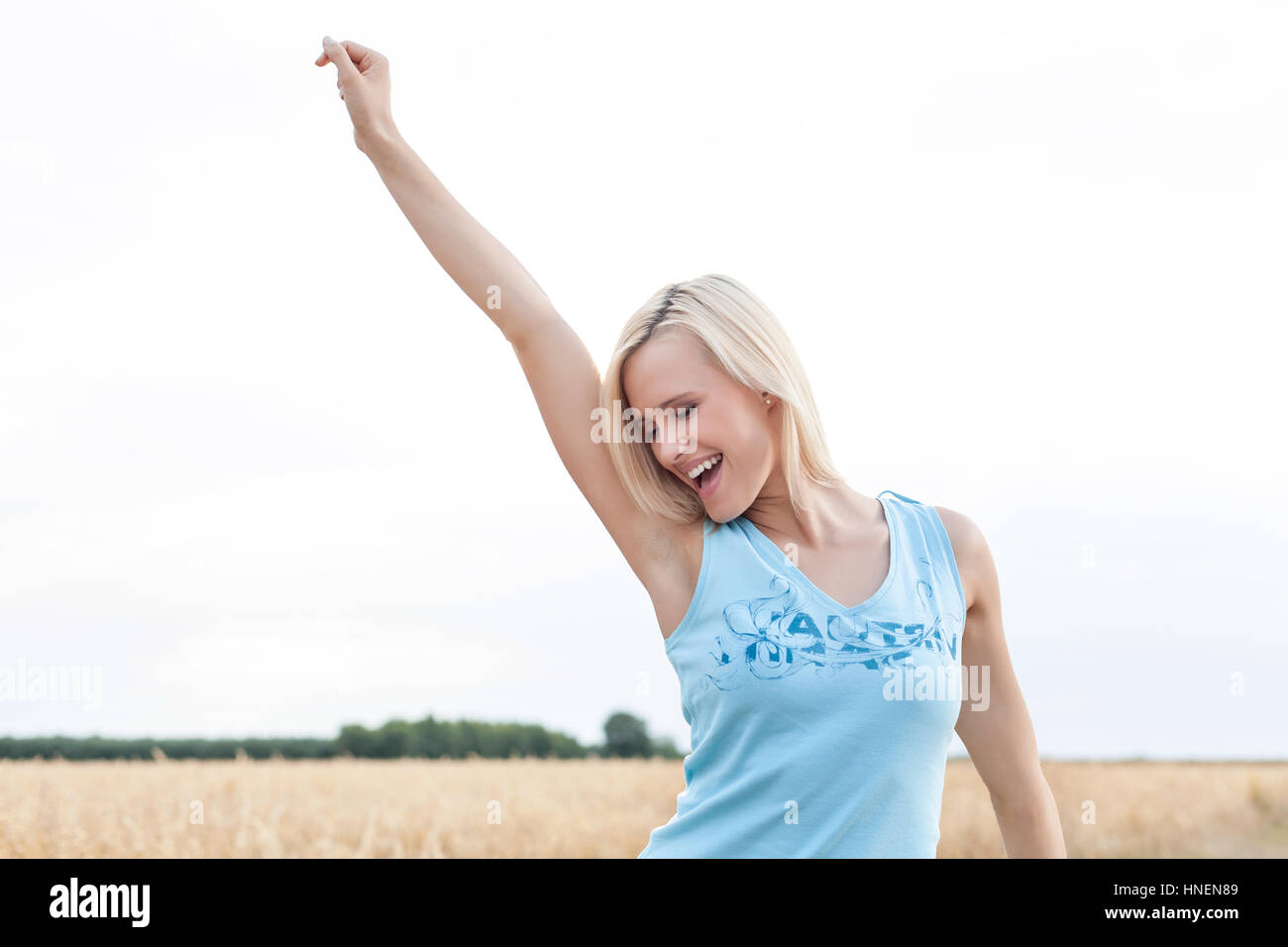 Cheerful young woman with arm raised standing against clear sky Stock Photo