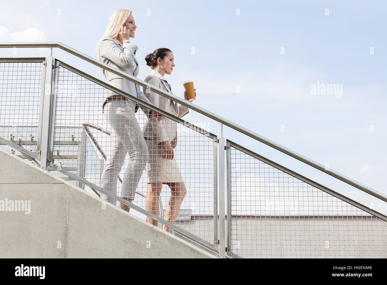 Profile shot of businesswomen moving down stairs against sky - Stock Image