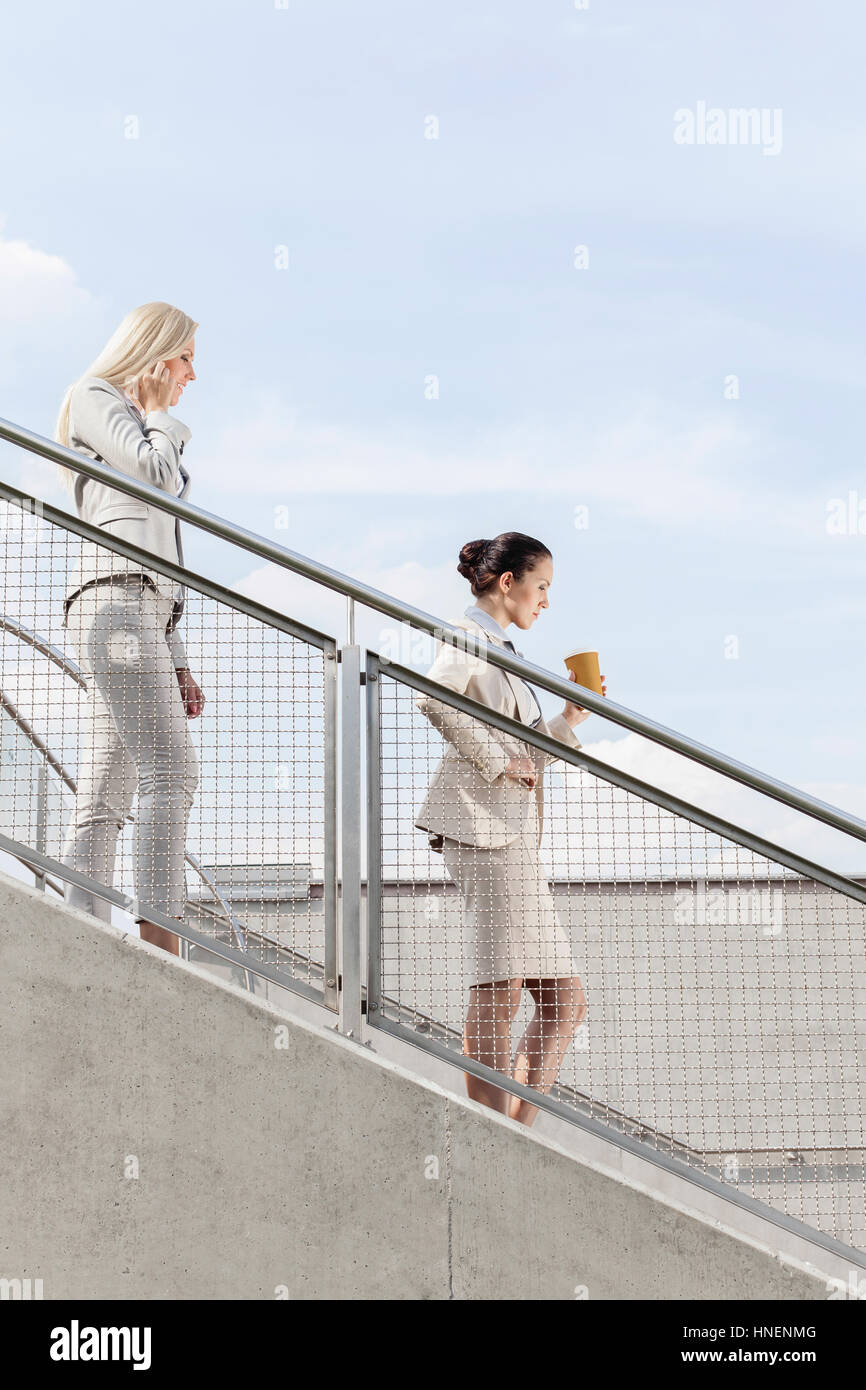 Profile shot of businesswomen moving down stairs together against sky - Stock Image