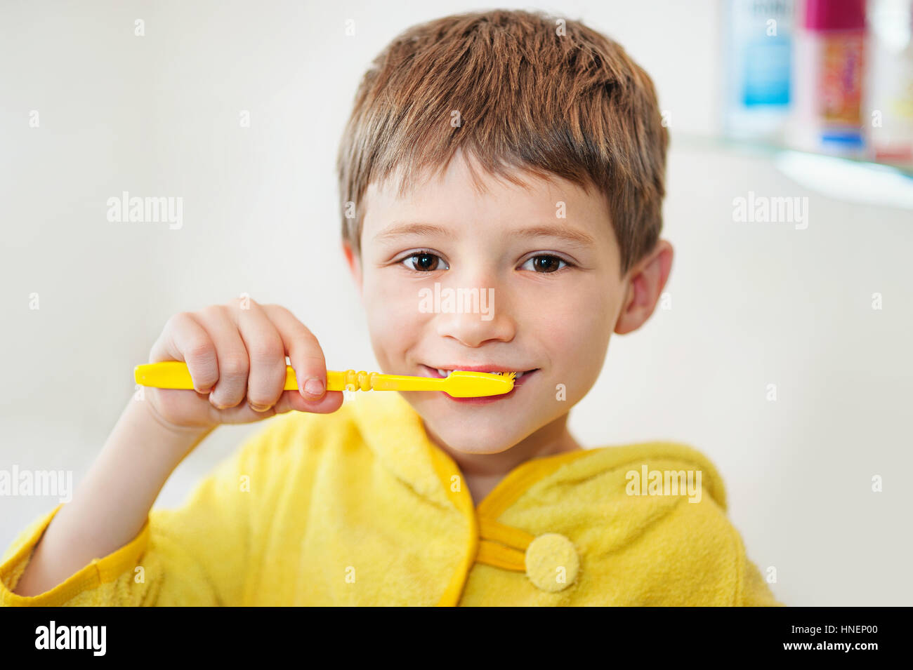 Boy brushing his teeth in bathtub, smiling, light grey background Stock Photo