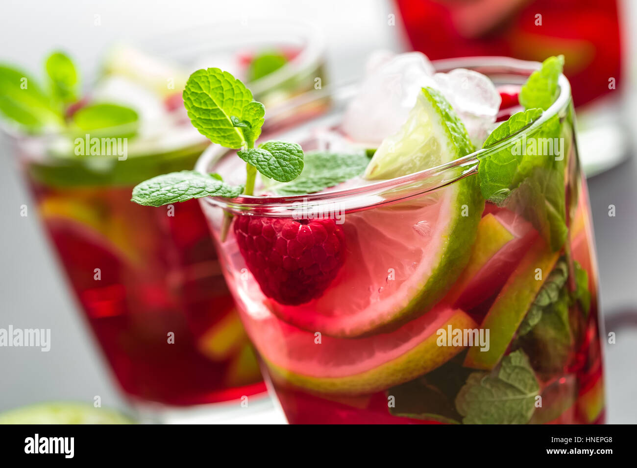 Raspberry mojito cocktail with lime, mint and ice, cold refreshing drink Stock Photo