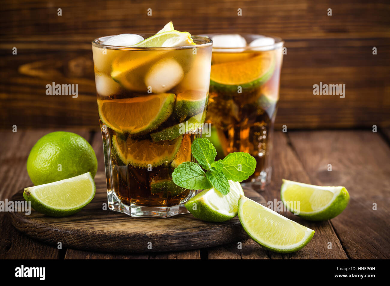 Cuba Libre cocktail with cola, lime and ice in glass, cold longdrink - Stock Image