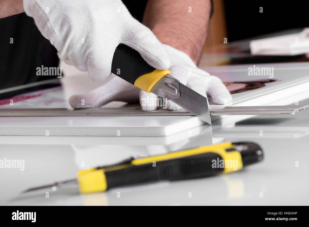 Professional hands in gloves cutting off edges of printed photography on white Foamex PVC panel board with another - Stock Image