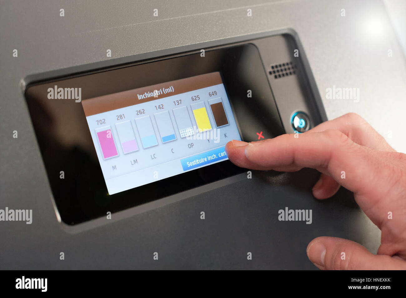 Man checking printer ink levels on a professional printer on a digital display in a print house - Stock Image