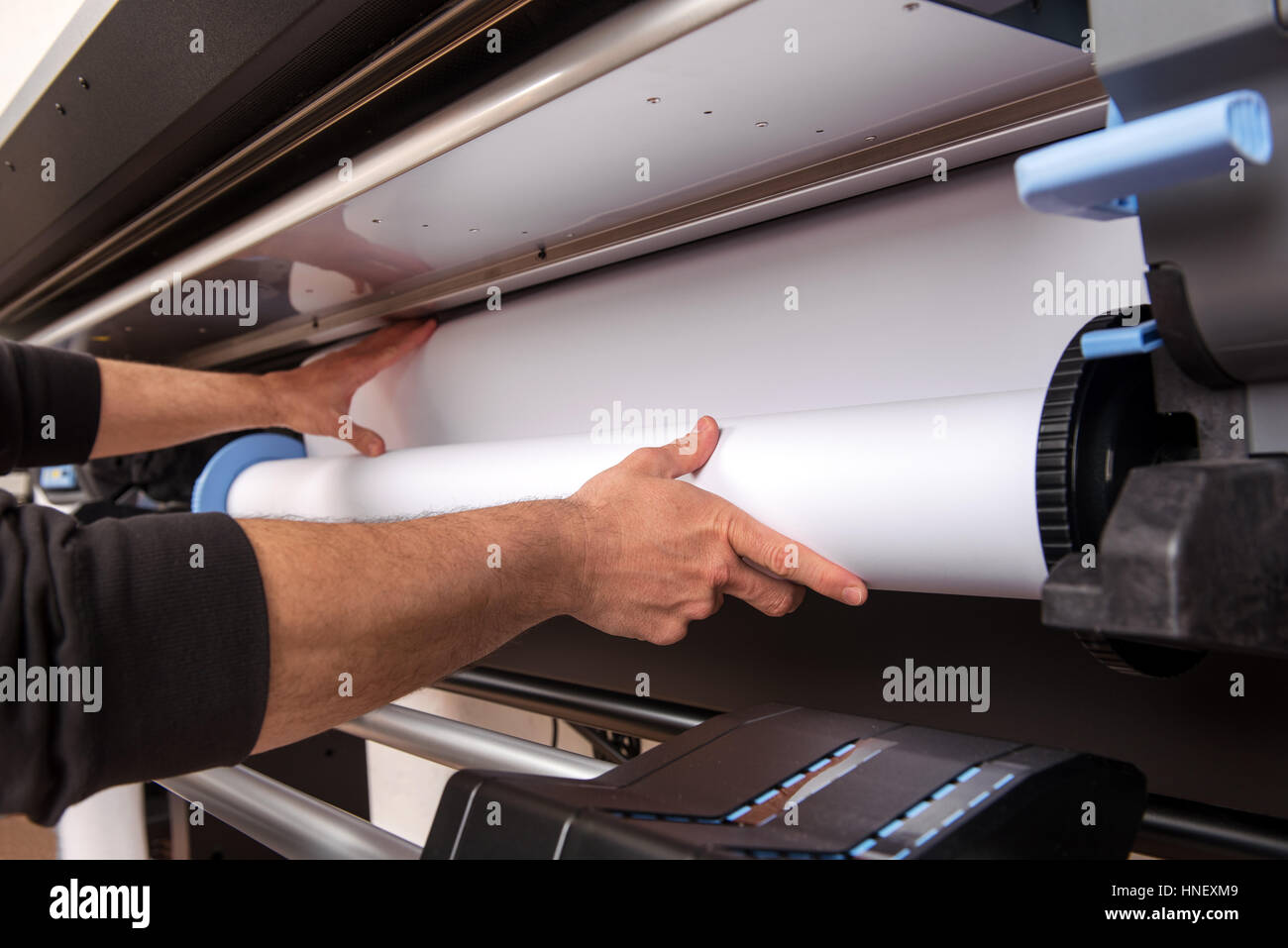 Close-up man hands loading wide format white paper roll on professional printer - Stock Image