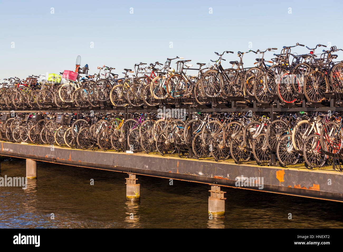 Bicycle parking lot on the river Het IJ, many bicycles in the bike racks, harbor area, Amsterdam, Province of North - Stock Image