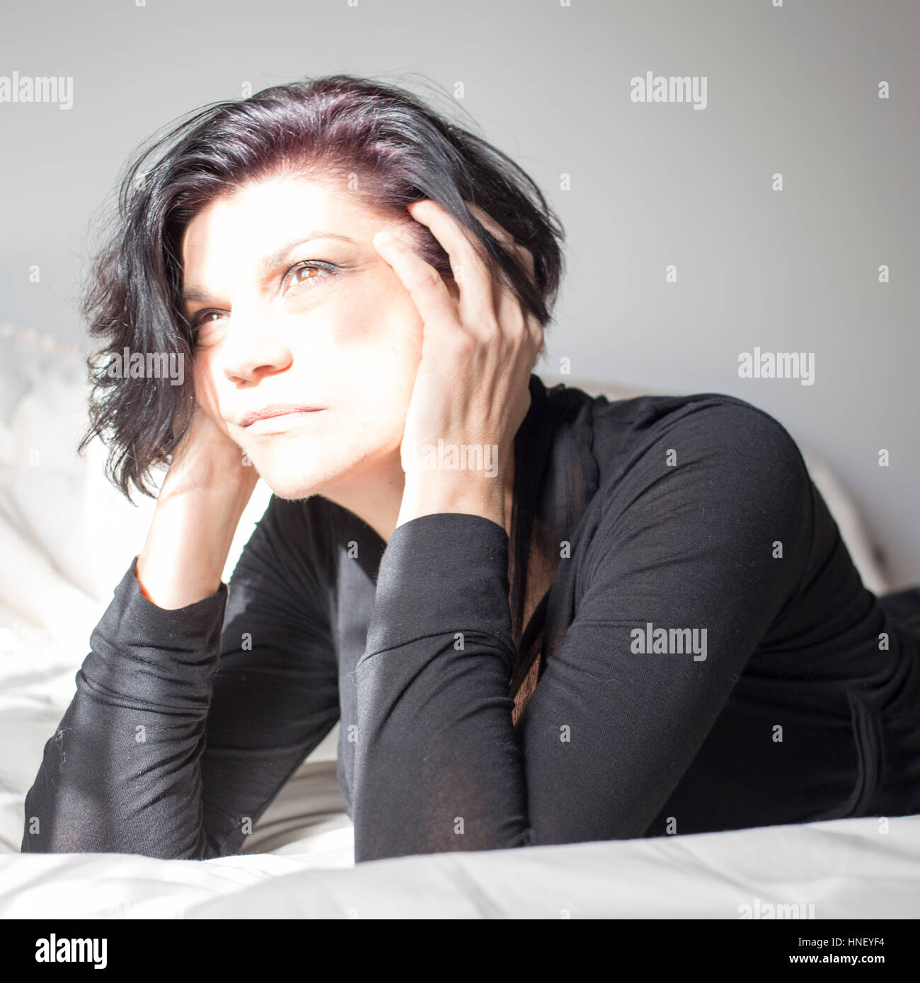 Unfocused shot of a woman in thought. - Stock Image