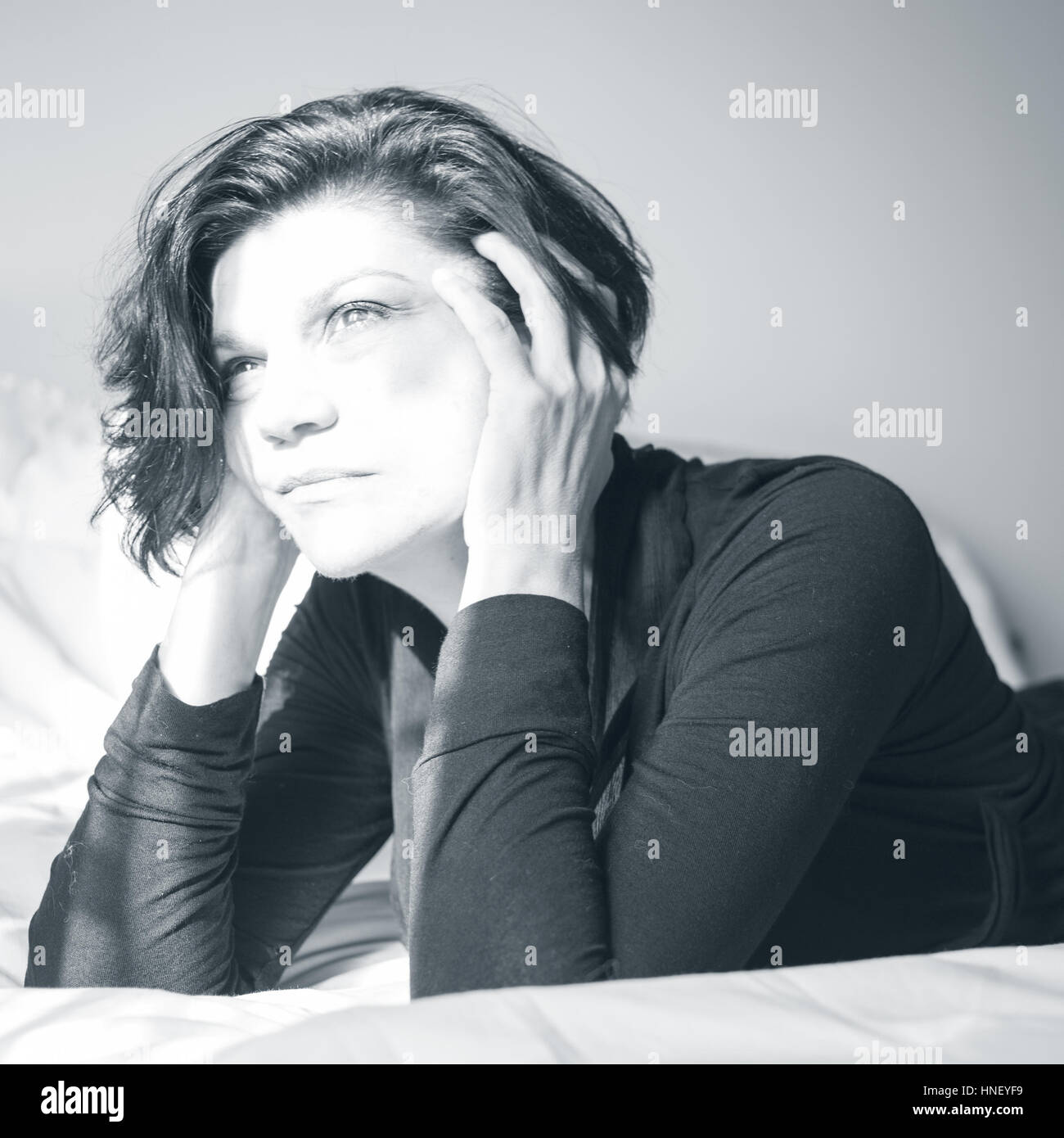 Unfocused shot of a woman in thought. Black and White. - Stock Image