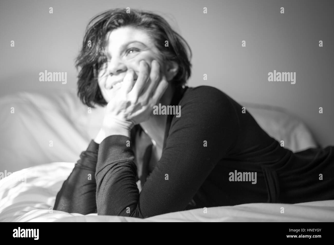 Unfocused shot of a smiling woman in black and white - Stock Image