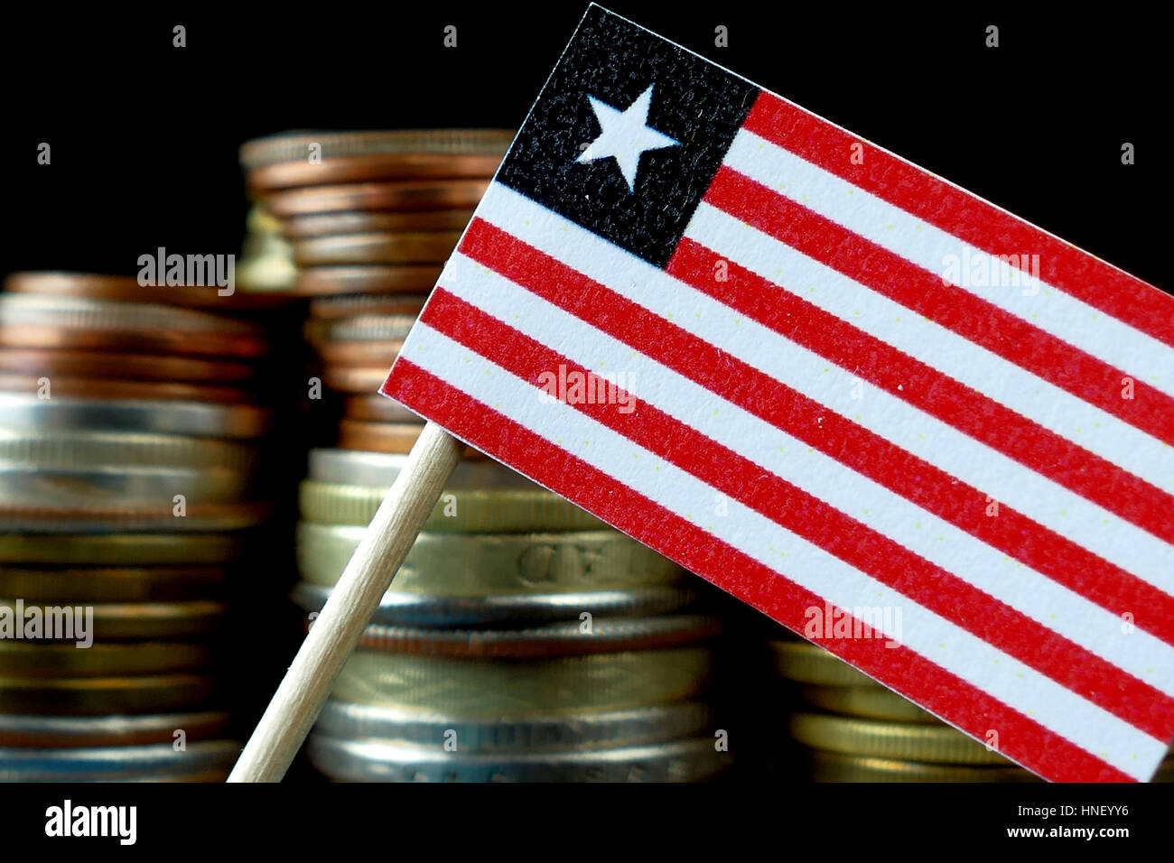 Liberia flag waving with stack of money coins macro - Stock Image
