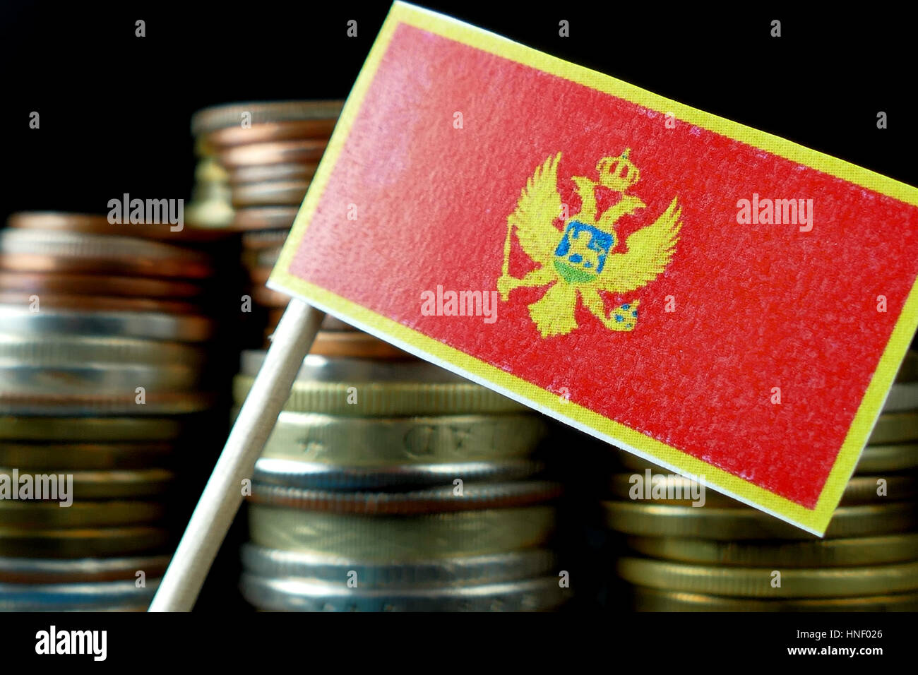 Montenegro flag waving with stack of money coins macro Stock Photo