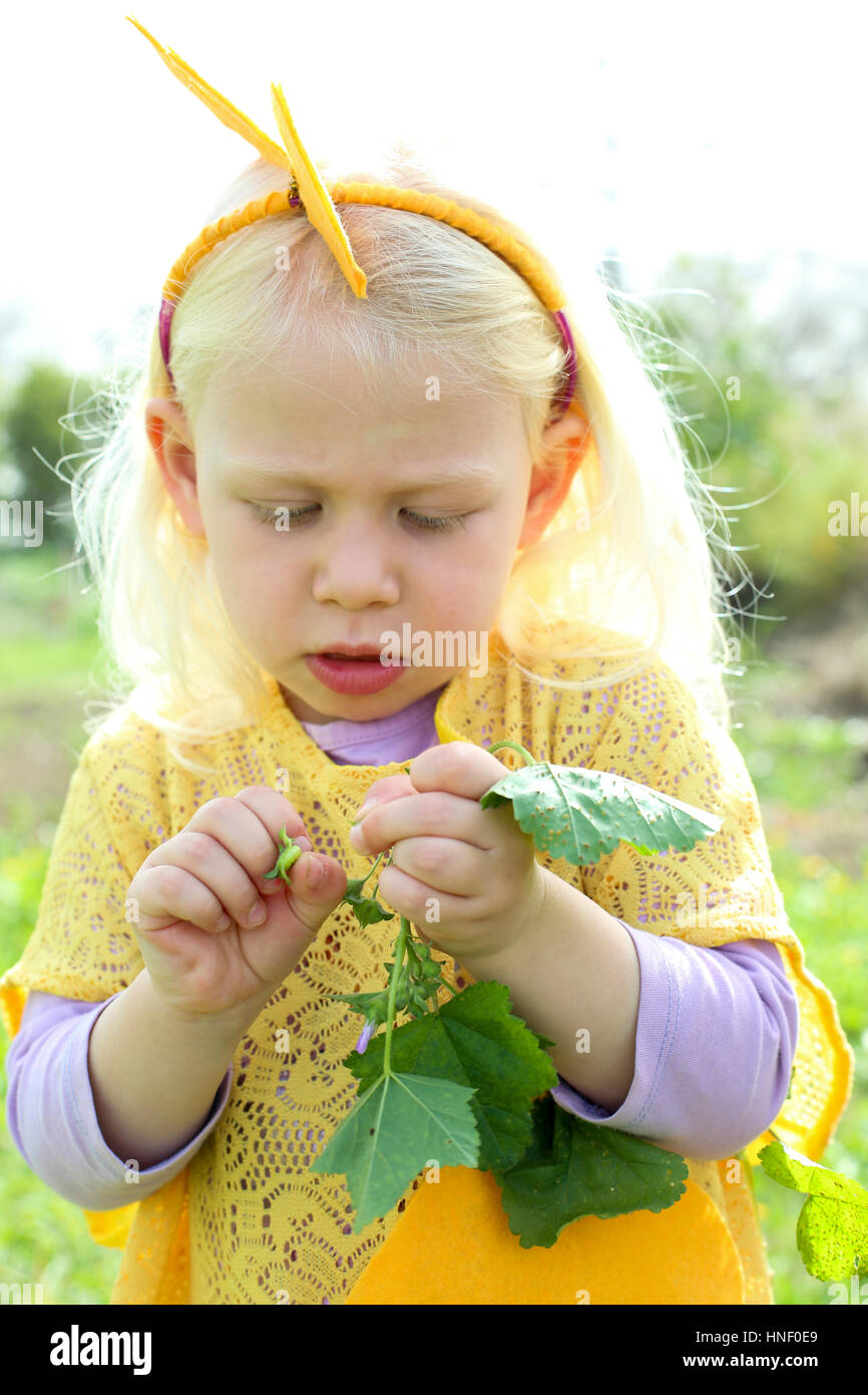 Young blond girl of four plays outdoors in an uncultivated field - Stock Image