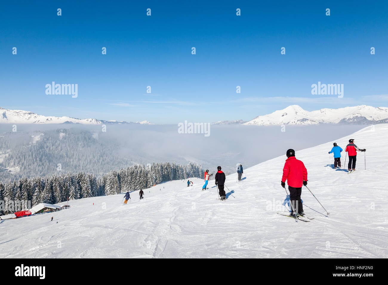 MORZINE, FRANCE - FEBRUARY 07, 2015: Skiers and snowboarders on La Combe piste in Morzine resort, part of the Portes - Stock Image