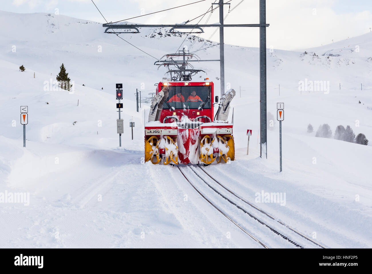 GRINDELWALD, SWITZERLAND - FEBRUARY 3, 2014 : A locomotive with snow blower attachments clears snow from the Lauterbrunnen - Stock Image