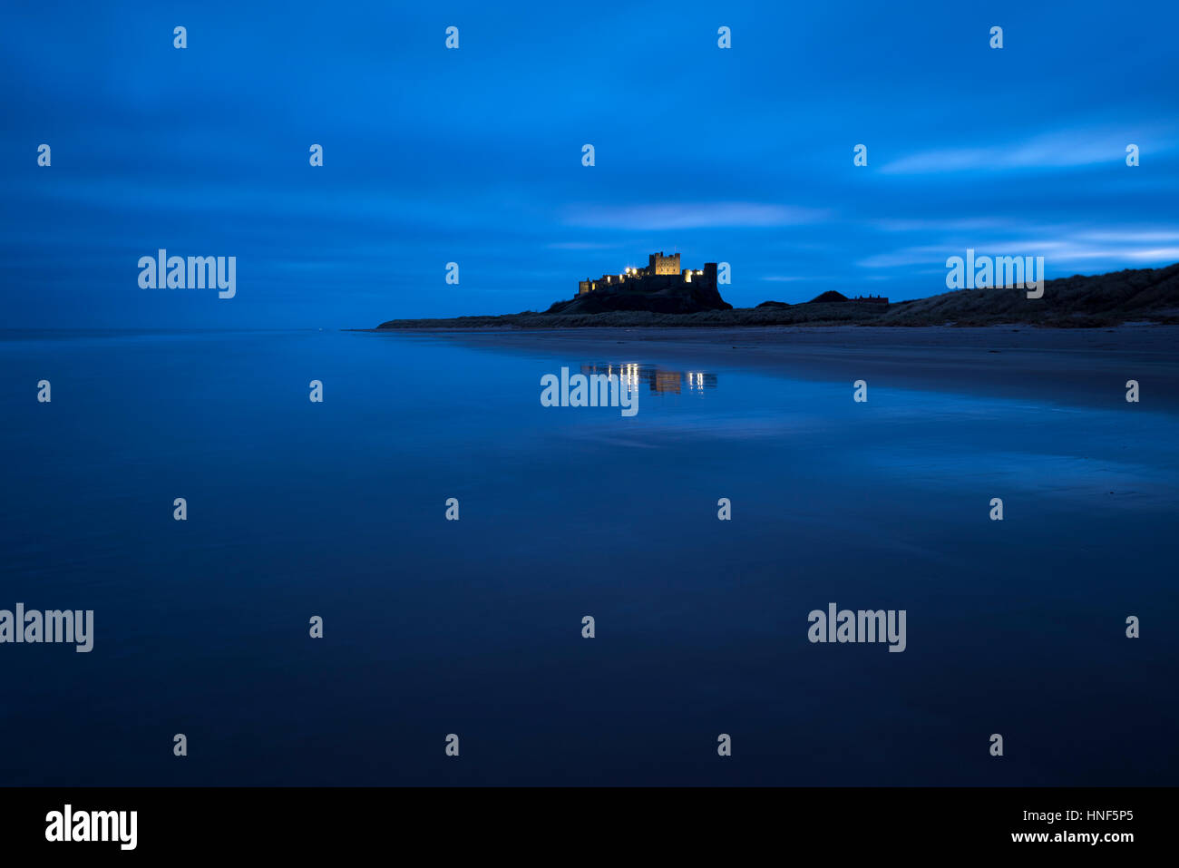 Bamburgh Castle lit up in the pre-dawn light on the Northumberland Coast. - Stock Image