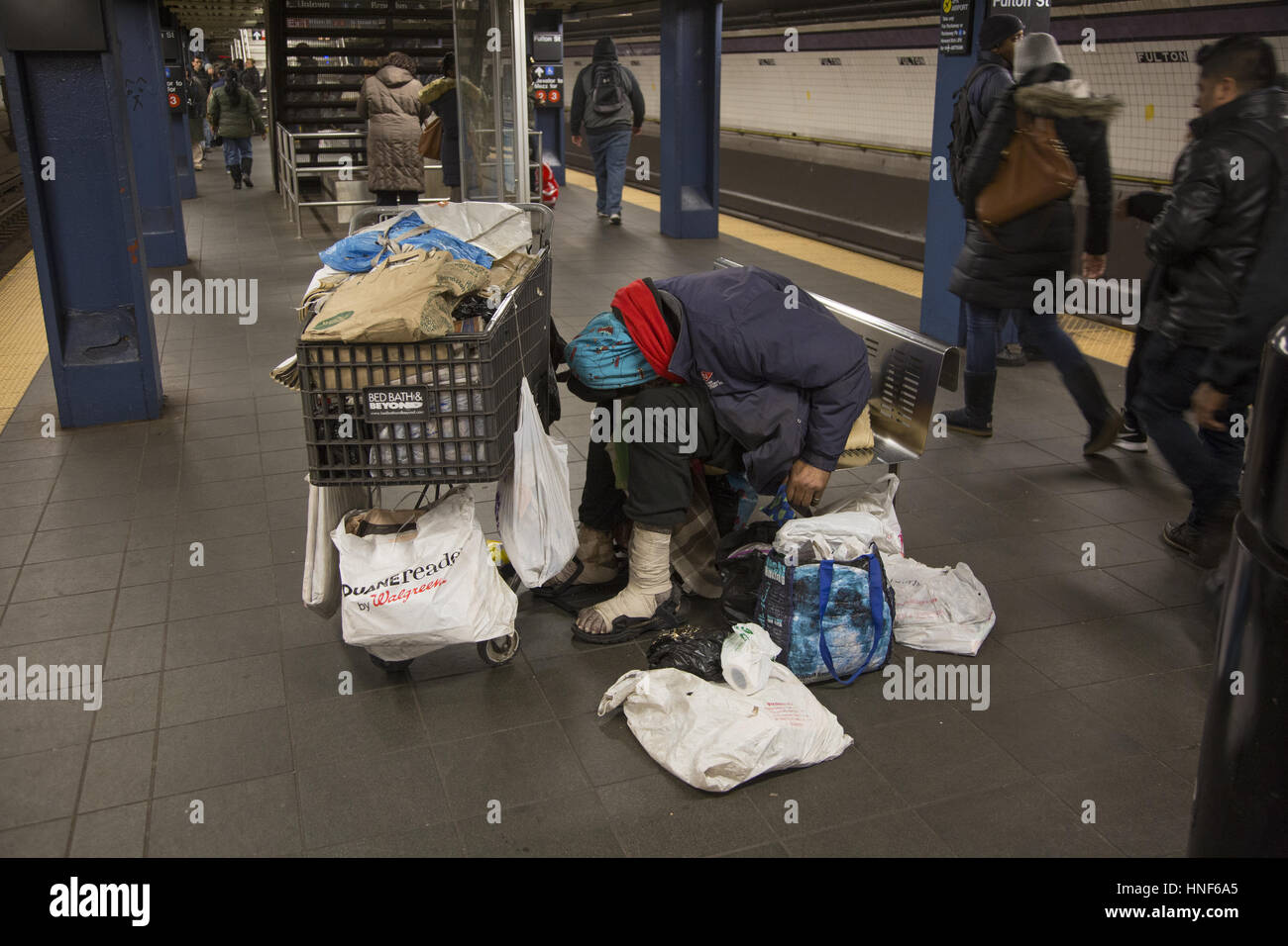 Mentally ill, homeless person sleeps on the train platform with his worldly possessions with him at Fulton Street - Stock Image