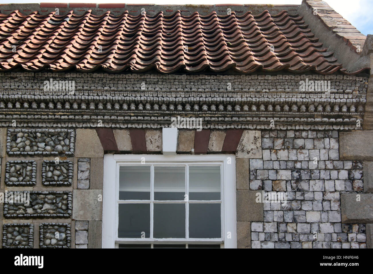 House in Cley Norfolk showing facade composed of whale bone vertebrae  together with knapped flint in a decorative - Stock Image