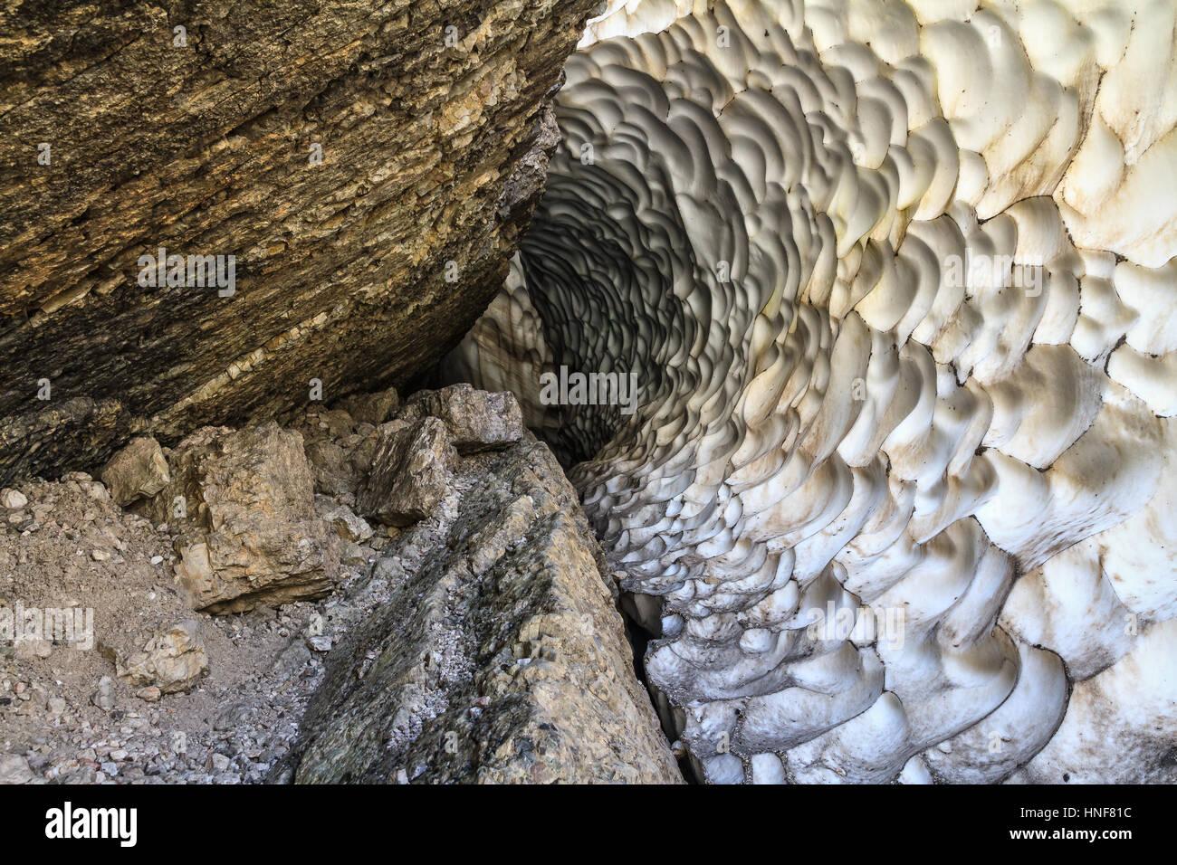 Dolomiti - tunnel between rocks and glacier called Grotta della Neve in Val Badia, Alto Adige, Italy - Stock Image