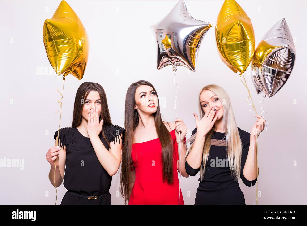 783a69e9671e Three lovely young women standing and holding star shaped balloons over  white background - Stock Image