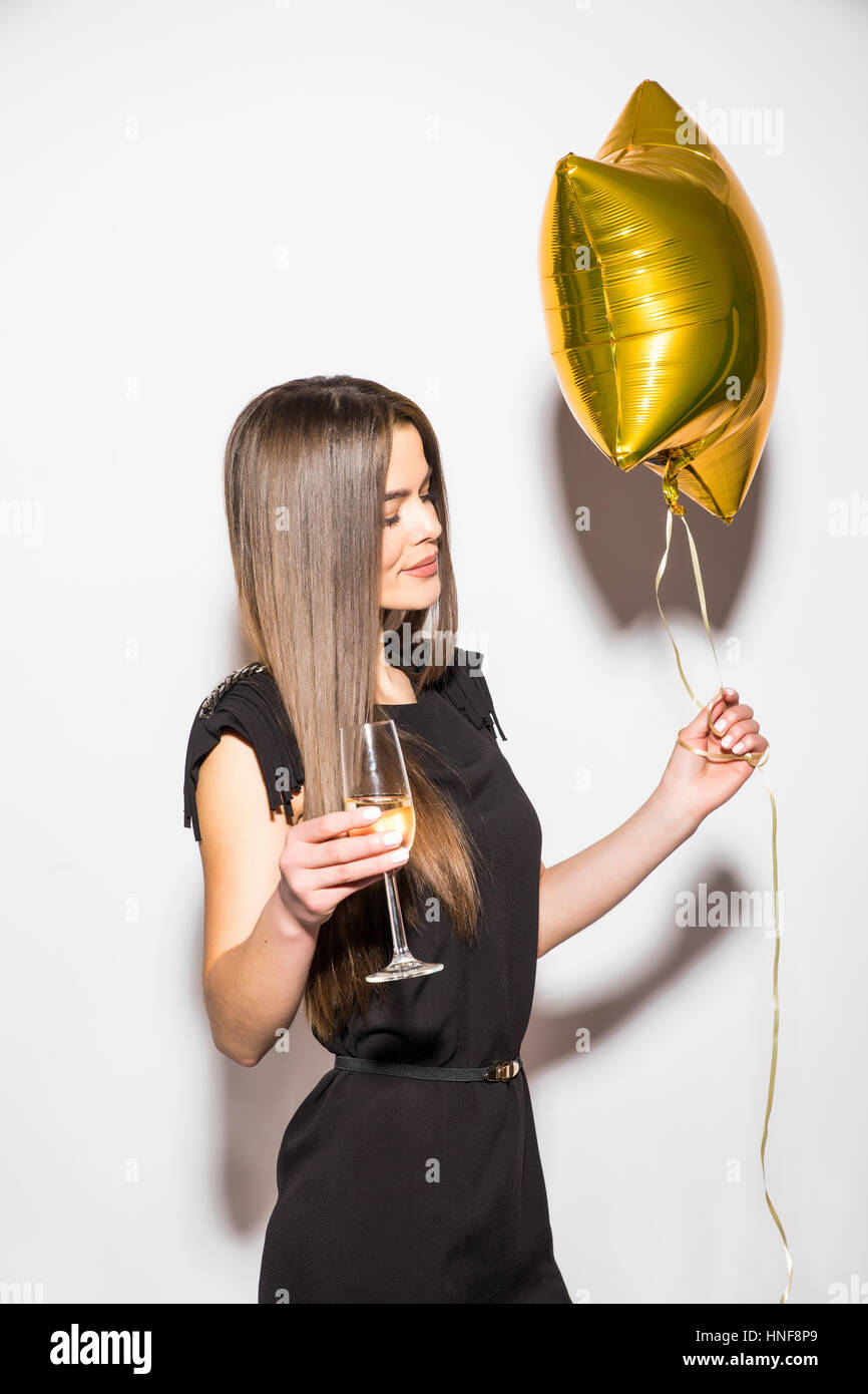 970291529f87 Happy attractive young woman in black dress holding star shaped balloon and drinking  champagne over white background