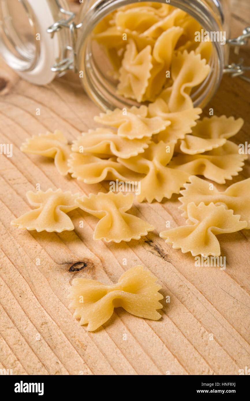 raw farfalle bow-tie pasta on wooden table - Stock Image