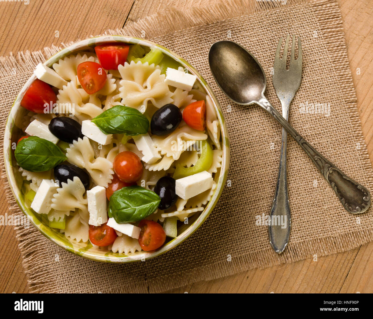 rustic farfalle salad in bowl on wooden table - Stock Image