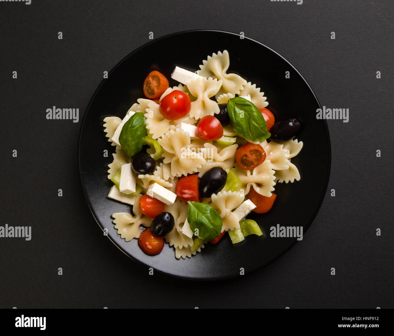 farfalle salad with tomato, basil, olive, pepper and cheese on black plate - Stock Image