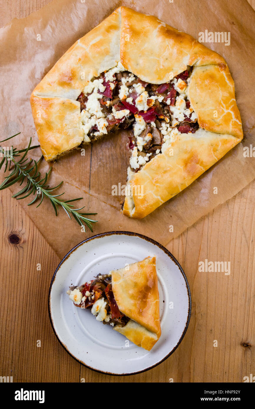 slice of galette with mushrooms, bacon and cheese, on rustic setting - Stock Image