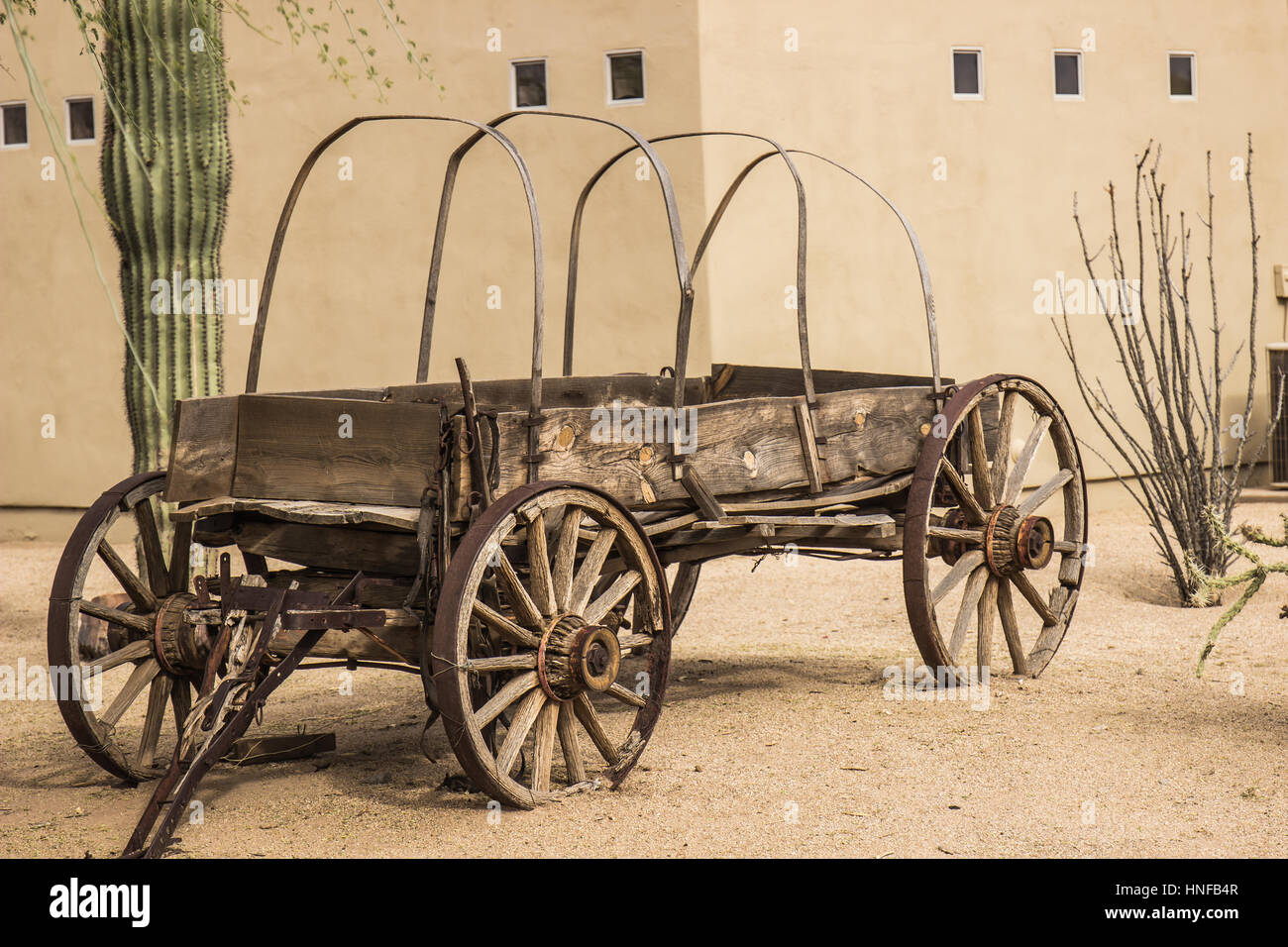Vintage Western Wagon In Front Of Abobe Building - Stock Image