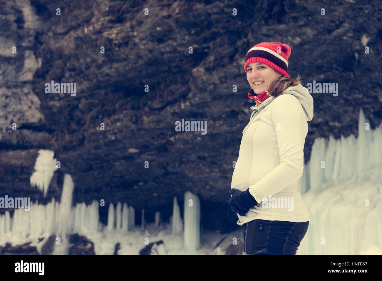 Young pregnant woman smiling on winter landscape. - Stock Image