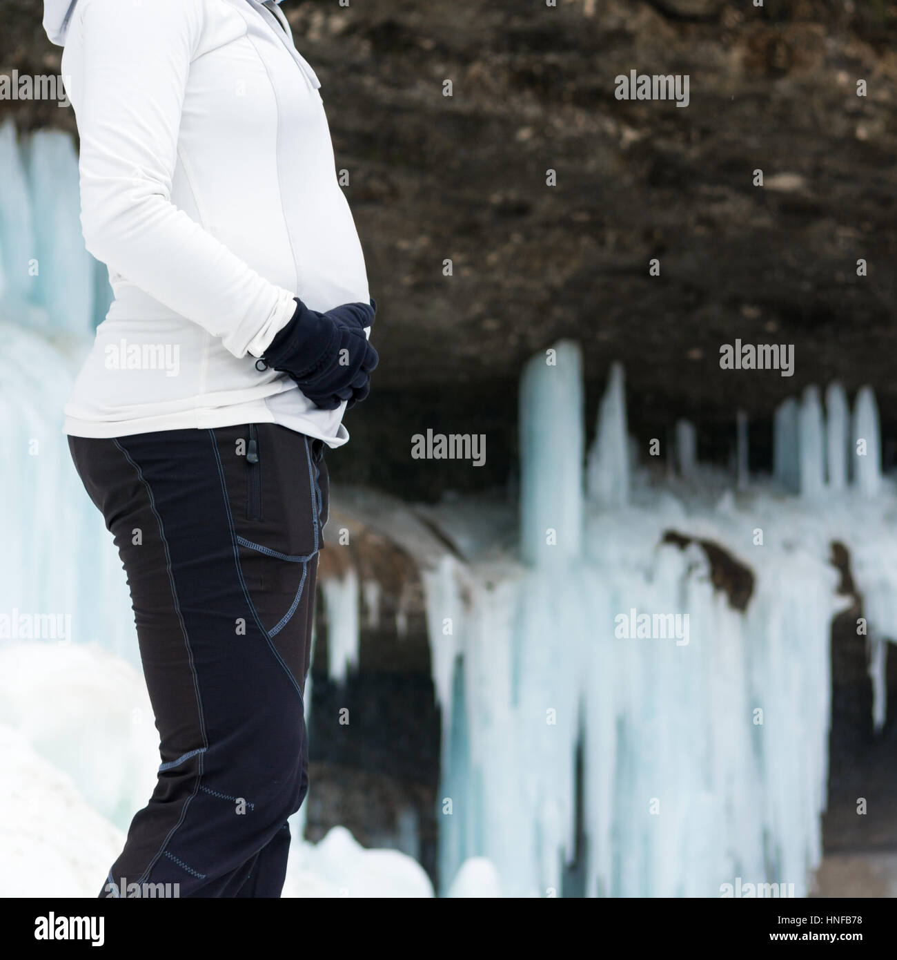 Closeup of female hands holding pregnant belly on winter background. - Stock Image
