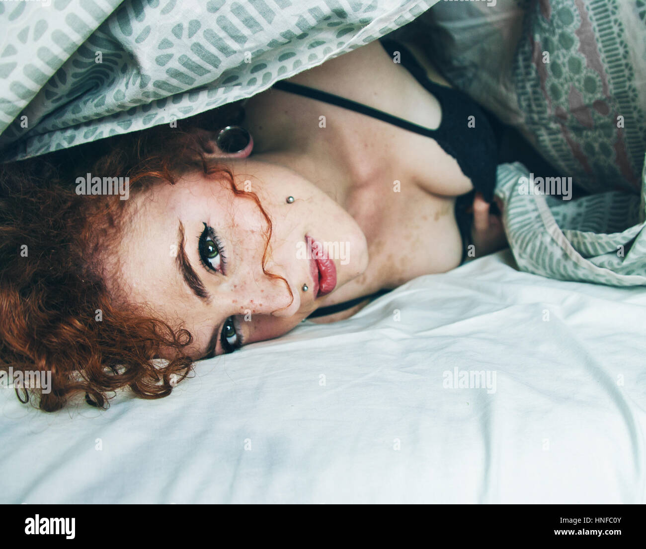 Portrait of a redhead young woman in her bedroom - Stock Image