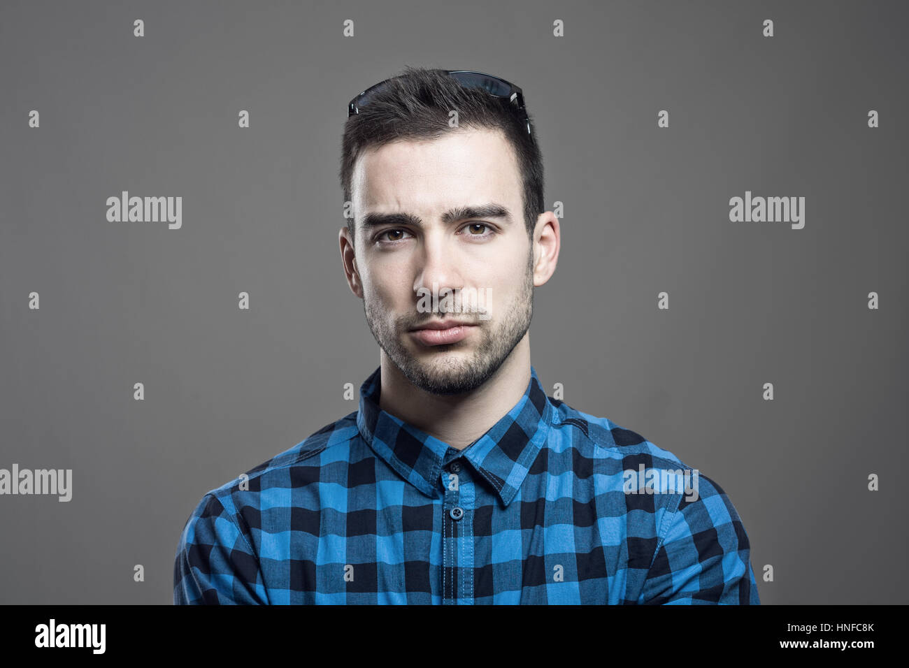 Moody portrait of skeptical young man frowning face looking at camera over gray studio background. - Stock Image