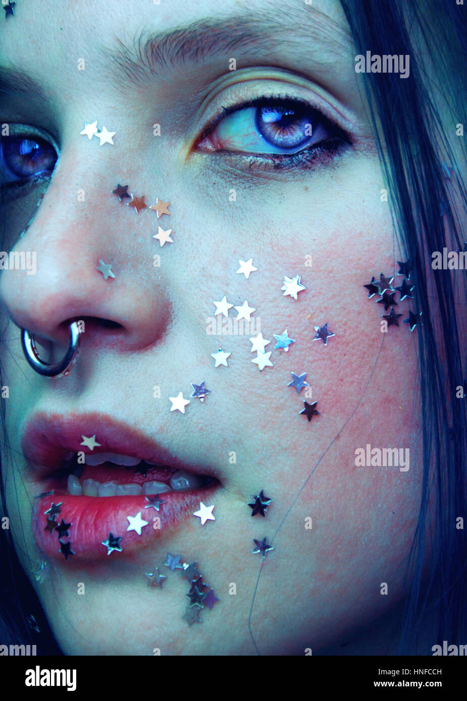 Artistic portrait of  a woman with her face covering with a lot of silver stars - Stock Image