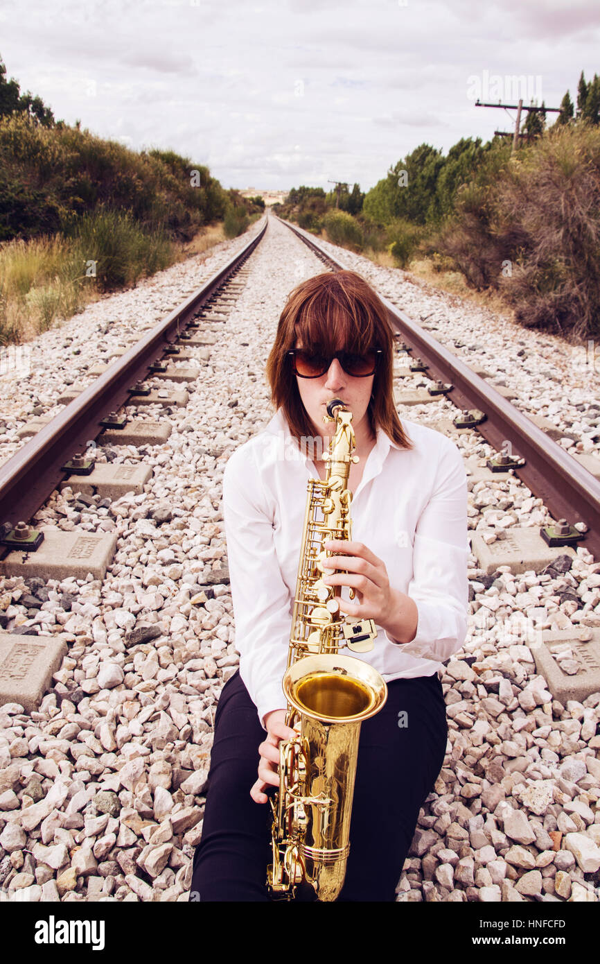 Young woman playing a saxophone - Stock Image