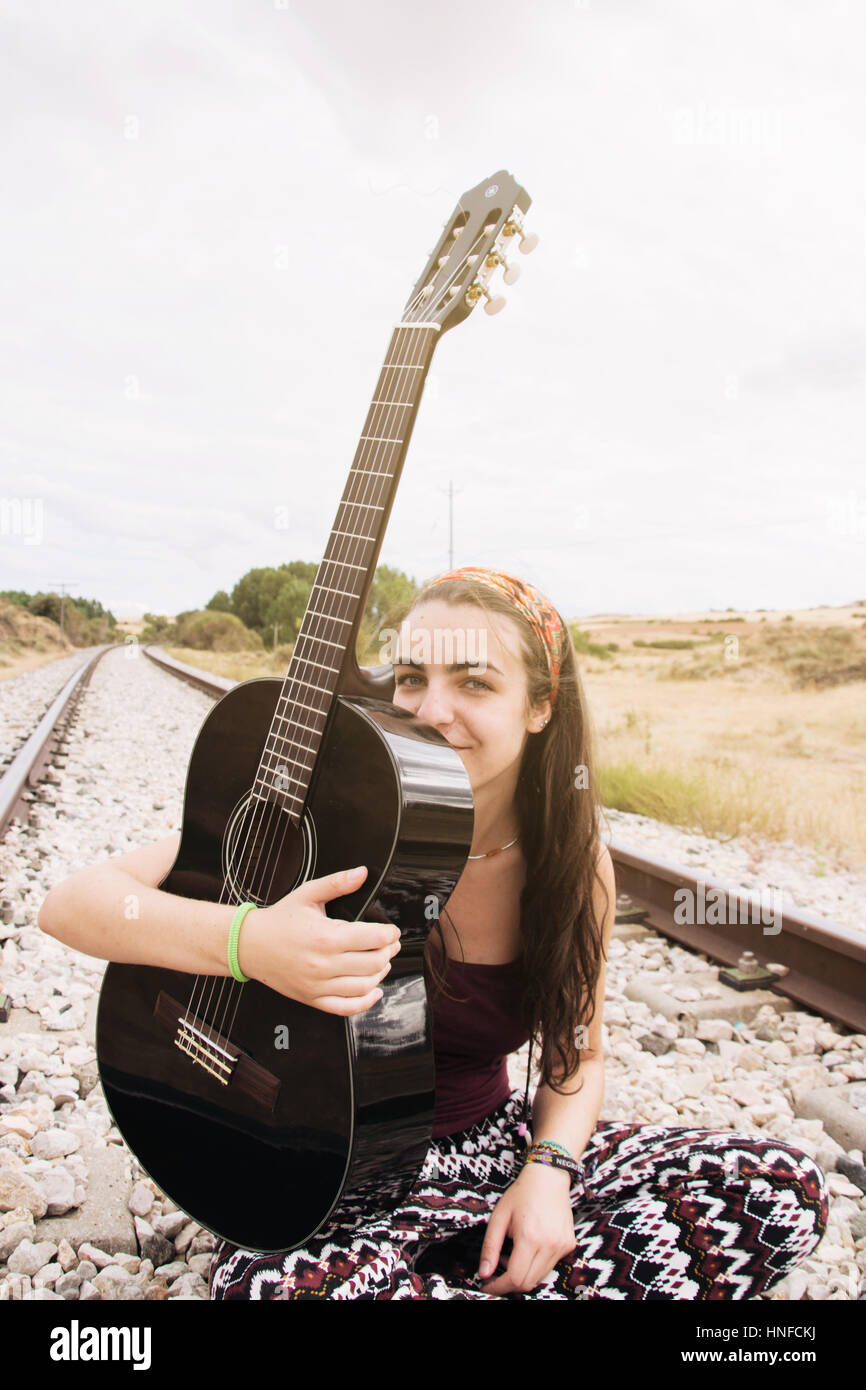 Teen woman in a railroad way with her guitar - Stock Image