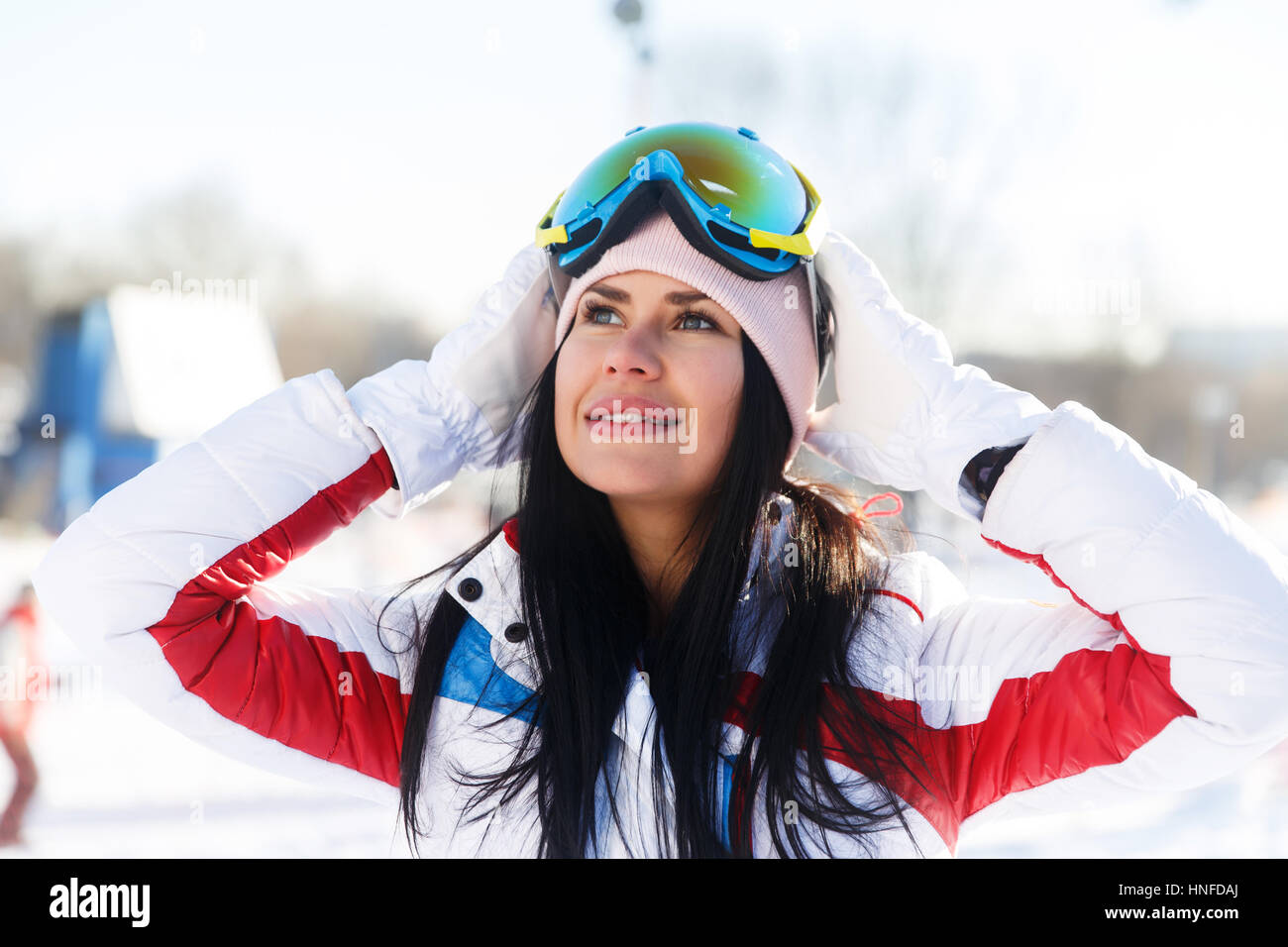 Long-haired brunette in ski suit on winter weekends - Stock Image
